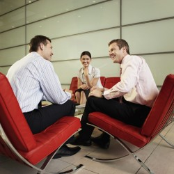 Smiling Businesspeople Having Meeting --- Image by © moodboard/Corbis